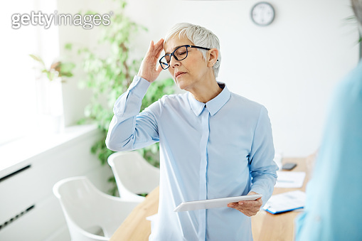 business businesswoman headache stress office senior gray hair problam pain woman tablet work