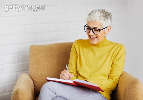 beautiful senior mature woman portrait gray hair writing notebook pen note work book cup coffee tea drink