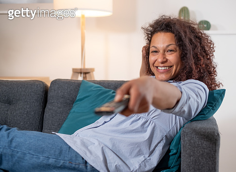 One black woman watching television on the sofa