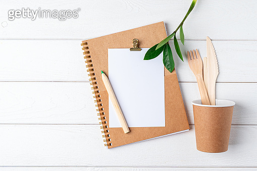 Desktop mockup planner. Flat lay of white wooden table background. Top view green sprout leaves, coffee cup, cutlery, blank, craft Notebook. Zero waste, eco friendly, natural organic concept
