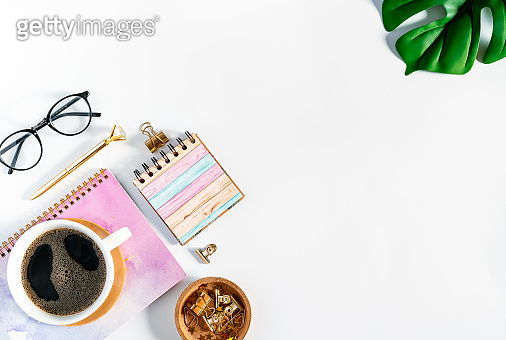 Flat lay of white working table place background with cup of coffee putting on it. Top view glasses, leaf, golden paper binder clips, Notebook and pen. Desktop mock up scene with copy space