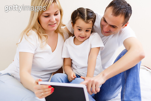 Family lying on a carpet with tablet in the living room