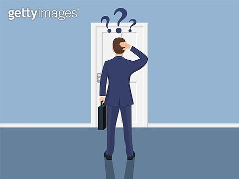 Businessman standing in front closed doors.