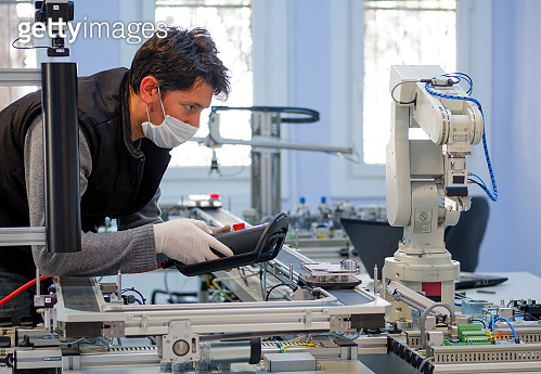 Man with surgical mask on face against COVID-19 ( Coronavirusis ) programming robot arm with control panel which is integrated on smart factory production line.