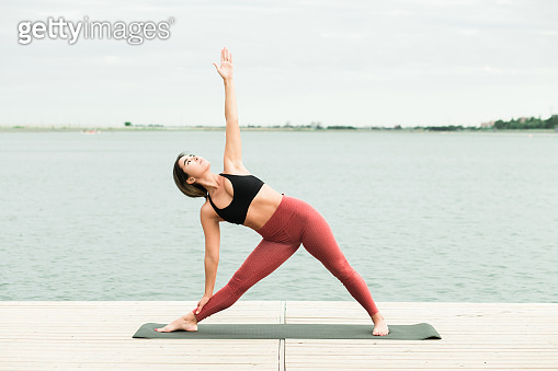 Asian young girl doing yoga outdoors on the pier by the lake.
