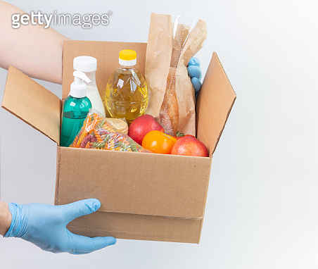 Person in latex gloves has holding a box with ordered goods. Safe food delivery service under quarantine. Online food shopping service or donation concept. White background.High quality close-up photo