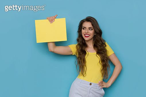 Beautiful Young Woman Is Showing Yellow Empty Sheet Of Paper And Looking At It.
