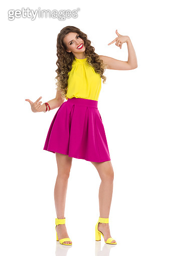 Young Woman In Vibrant Clothes Is Pointing At Herself. Front View.