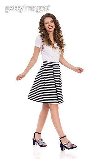 Walking Woman In Striped Skirt And High Heels. Side View.