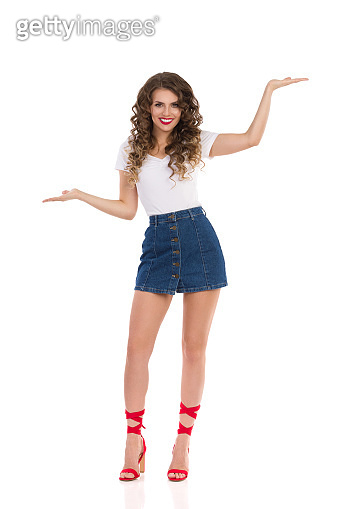 Young Woman In Mini Skirt And High Heels Holds Hands Raised And Compares Something