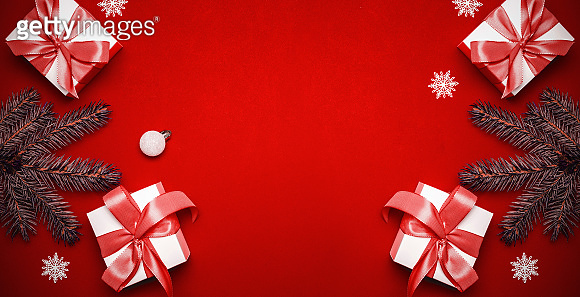 Christmas decoration red background. White gifts with scarlet bow, red balls and sparkling lights in xmas decoration on reddish background for greeting card. Flat lay, top view, copy space.