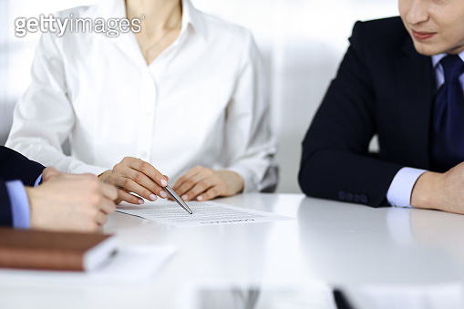 Group of business people, men and a woman, discuss details of a contract at meeting in a modern office. Discussion at negotiation or workplace. Teamwork, partnership and business concept