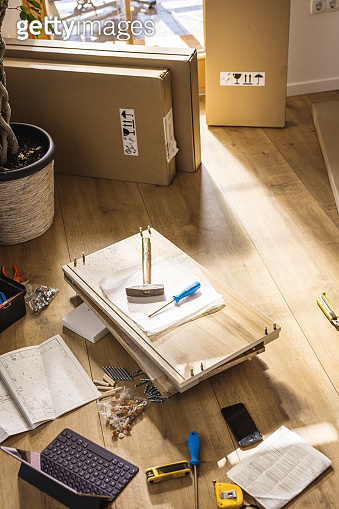 Flat-pack furniture and tools on floor at home