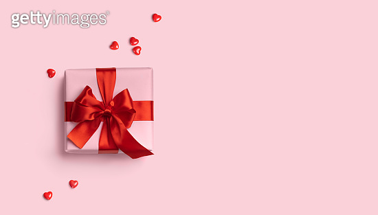 Pink gift box with red bow on pink background with red hearts around. Holiday web banner. Top view. Flat lay. Copy space