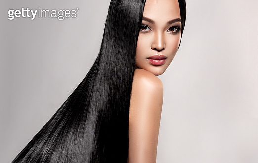 Black haired young woman with asian appearance is demonstrating dense, well cared, straight hair. Oriental beauty.