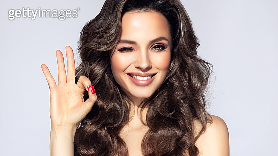 Young, brown haired woman with voluminous hairstyle is showing sign of success, wide toothy smile on her face.Promotion and advertisement.