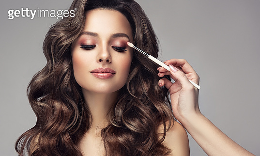 Hand of makeup artist is coloring eyelid of lovely model. Excellent hair waves. Makeup, hair care and hairdressing art.