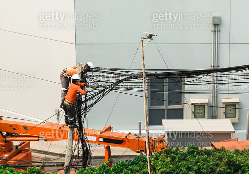 Electricians Engineer are climbing on electric poles