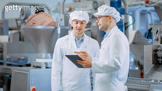 Two Young Food Factory Employees Discuss Work-Related Matters. Male Technician or Quality Manager Uses a Tablet Computer for Work. They Wear White Sanitary Hat and Work Robes.