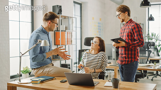 Shot of Young Woman and Two Male Colleagues Having Friendly Meeting and Discussing New Business Ideas. Easygoing Coworking Atmosphere in Loft Office Creative Agency. They Make Notes in Laptop, Tablet.