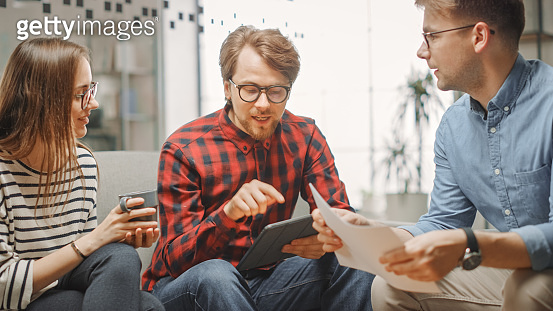 Young Woman and Two Male Colleagues Having a Friendly Meeting and Discussing New Business Ideas. Easygoing Coworking Atmosphere in Loft Office Creative Agency. They Look at Papers and Tablet.