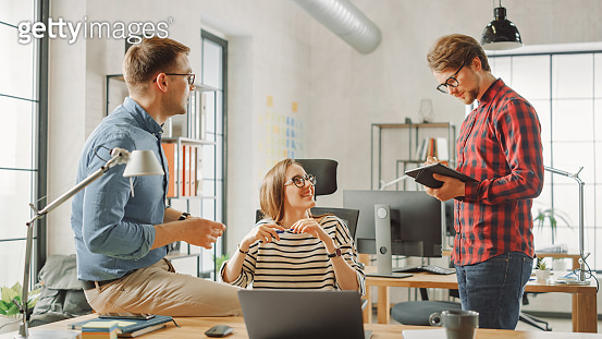 Young Woman and Two Male Colleagues Having a Friendly Meeting and Discussing New Business Ideas. Easygoing Coworking Atmosphere in Loft Office Creative Agency.