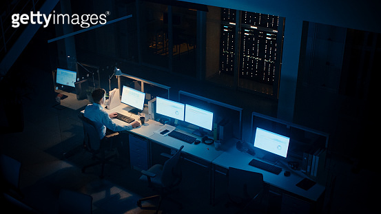 Working Late at Night in the Office: Businessman Using Desktop Computer, Analyzing, Using Documents, Solving Problems, Finishing Project. High Angle Shot