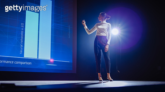 On-Stage Successful Female Speaker Presents Technological Product, Uses Remote Control for Presentation, Showing Infographics, Statistics Animation on Big Screen. Live Event / Business Conference