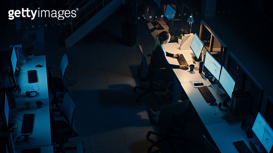Working Late at Night in the Office: Businesswoman Using Desktop Computer, Having Discussion, Analyzing, Using Documents, Solving Problems, Finishing Project. High Angle Shot