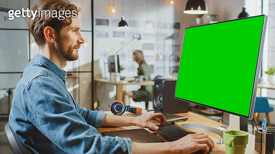 Male Creative Designer with Beard and Jeans Shirt Works on His Personal Computer with Big Green Screen Mock Up Display. He Works in Cool Office Loft. Female Creative Colleague Works in Background.
