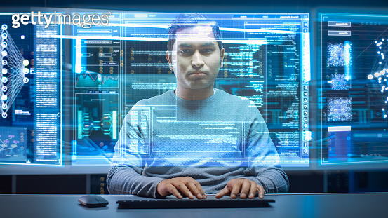 Portrait of Software Developer / Hacker Wearing Glasses Sitting at His Desk and Working on Futuristic Transparent Computer in Digital Identity Cyber Security Data Center. Hacking or Programming.