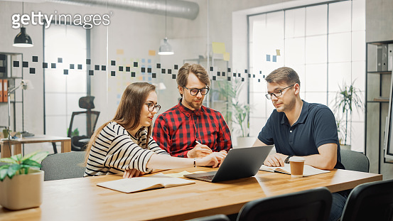 Young Woman and Two Male Colleagues Having a Friendly Meeting and Discussing New Business Ideas. Easygoing Coworking Atmosphere in Loft Office Creative Agency. They Make Notes in Laptop and Tablet.