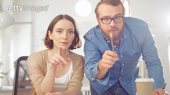 Portrait Shot of a Man and a Woman Discussing Work Looking Straight at the Camera. They are Working in the Brightly Lit Modern Office.