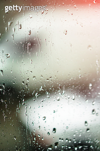 Window overlooking a rainy street. Gloomy evening weather with a view of the road. Drops on glass and bokeh from cars. Stock background for design