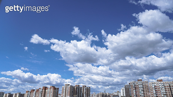 Apartment buildings on a background of beautiful clouds. High-rise buildings are built with panel construction in which people live. Stock photo background