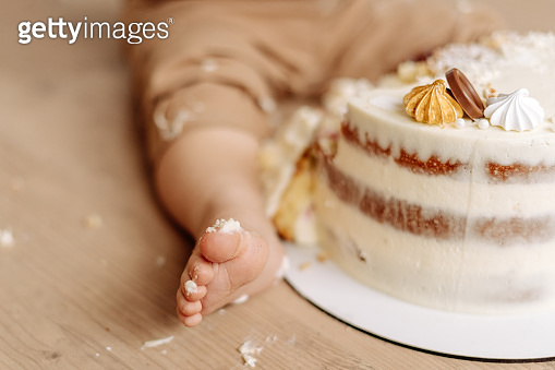 Child Leg in Cream and 1st Birthday Frosting Cake