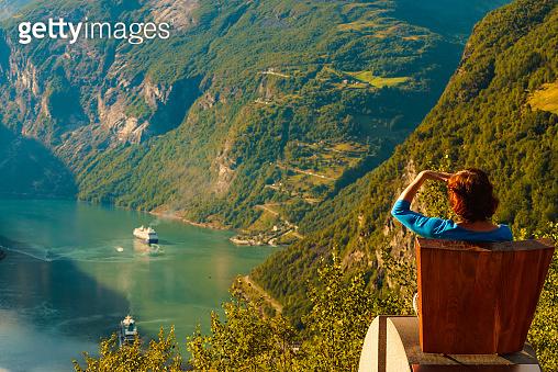 Tourist enjoy Geiranger fjord from viewpoint seat
