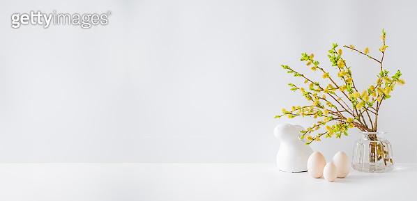 Home interior with easter decor. Willow branches in a glass vase, easter eggs on a light background