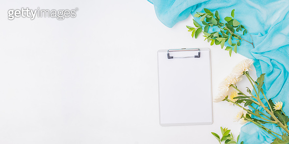 Flat lay home office desk workspace with mockup clipboard, scarf, flowers, branches with green leaves on white background