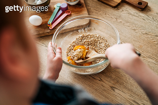 Person mixing ingredients in a bowl baking at home