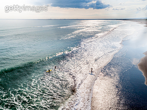 Aerial view of a beach and surfers