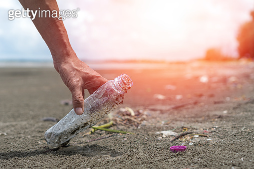 CSR Corporate Social Responsibility ecology concept. Hand of volunteer pick plastic bottle garbage on dirty beach to clean up nature environment.