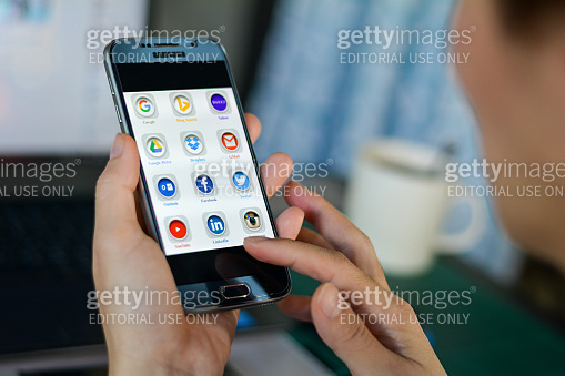 Bangkok, THAILAND - December 22, 2016: Woman lifestyle relaxing using smartphone with icons of social media on screen, smart phone life style, mobile phone era in everyday life