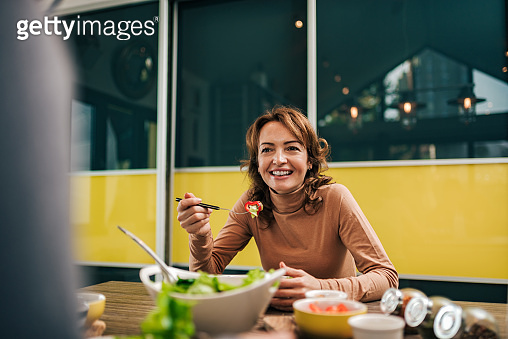 Portrait of a woman eating healthy meal at home.