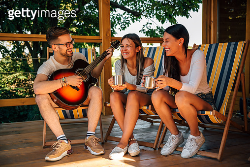 Young man playing guitar and two young women laughing. Friends on a summer holiday at countryside.