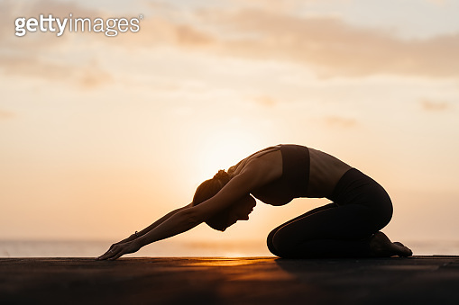 Yoga at sunset on the beach. woman performing asanas and enjoying life on the ocean