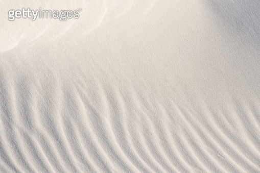 Light patterns on the sand of dune. Sand texture. Sandy beach for the background. Top view. Background, sand, light, beige, wave, reflect, shadow, summer.