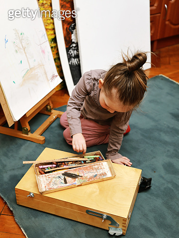 girl paints on an easel with pastel