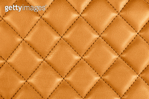 Modern luxury car brown leather interior. Part of perforated leather car seat details. Orange perforated leather texture background. Texture, artificial leather with diagonal stitching. Leather seats