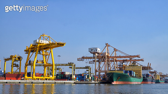 Logistics and transportation of Container Cargo ship and Cargo plane with working crane bridge in shipyard at sunrise, logistic import export and transport industry